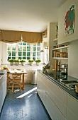 Schmale Küche - Küchenzeile mit weissen Schränken und Essplatz mit Kräutertöpfen auf Fenster
