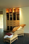 A dressing room with a wicker chair and a side table in front of a built-in, illuminated cupboard