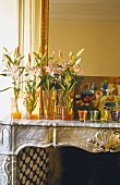 An arrangement of lilies in an orange vase and tea lights on the mantelpiece
