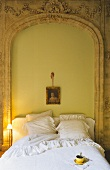 A bed against a bricked up archway set with breakfast coffee in an elegant apartment