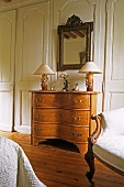 Table lamps on a Rococo chest of drawers with a mirror hanging above it in front of a wood panelled wall