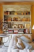 Antikes offenes Buffet mit Büchern vor farbiger Wand und helles Polstersofa
