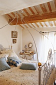 A white metal four poster bed with a bedside table in an attic bedroom with a wood beam ceiling