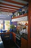 A mini kitchen with mahogany cupboards and tiled walls