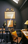 Under the roof - a dark grey wall hung with gold-framed pictures and an office corner on the landing