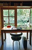 Arbeitstisch mit Lederstuhl aus Bauhauszeit vor geöffneter Terrassentür mit Gartenblick