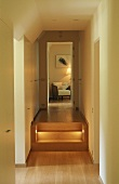 A hallway with illuminated steps and a view through an open door onto an armchair