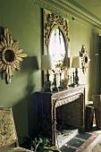 An elaborate mirror hung on a green wall above a mantelpiece