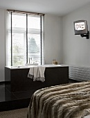 A fur cover on a bed with a free-standing grey bathtub in front of a window