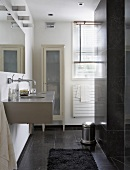 A designer bathroom with a grey tiled floor, a modern basin, a mirror and a country house-style cabinet