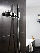 Designer taps with a shower head on a grey-tiled shower wall