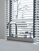 Designer bath taps in front of a window with half open blinds