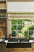 A kitchen in a country house with a view of the garden - a stone sink and brass taps in front of a transom window with a blind