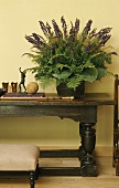 A flower arrangement with purple flowers on a rustic side table in front of a yellow wall