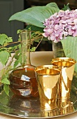 Still life on a silver tray - brass cups with a carafe of wine and flowers