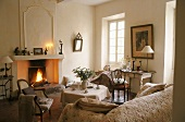 A light coloured living room in a country house with antique chairs and a table in front of a fireplace