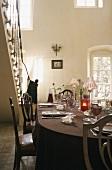 Gedeckter Tisch vor Treppe im offenen Raum mit Terrassentür