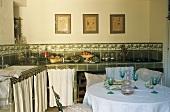 Landhausküche - Weingläser auf Tisch vor Küchenzeile mit grünen Fliesen und geschlossenen Vorhängen vor Unterschränken