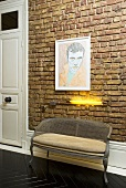 A wicker Rocco-style bench and a yellow light on a brick wall
