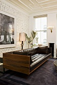 An elegant leather sofa with a wooden frame in front of a white brick wall