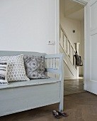 Gray bench with pillows and a view through an open door into the hallway of a country home