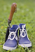 Blue galoshes and garden trowel