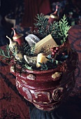 A red ceramic pot stuffed with Christmassy things