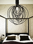 A hanging lamp wrapped with black draw cords over a canopied bed in front of wall with wall paper
