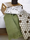 Wooden tray on a bed with pillows and patterned bedspread