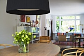 Black lampshade above flowers in a vase on a wooden dining table and an open plan living room