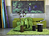 Flowers in vase and a black stool on a fluffy green rug in front of a green sofa with a quilt