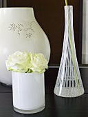 Assorted vases and white roses on a black surface