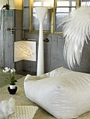 White pouf pillow and white floor lamp