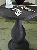 Black bistro table with paint tubes and paint brushes