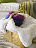 Basket with sheepskin throw blanket, balls of wool and knitting needles