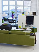 Green sofa and black upholstered stool with white entertainment center in front of patio doors