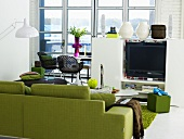 Green sofa and half height white entertainment center with flower vases in front of patio doors