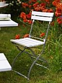 Weisser Klappstuhl im Garten mit roten Blumen