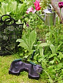 Knee pad and black plastic hand tote in front of a flower bed with watering can hanging from a tree