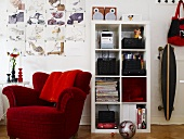 Red upholstered chair and white shelves and a skateboard on the wall