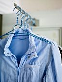 Coat hangers with a bright blue wind breaker hanging on a rack