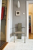 Designer metal stool in front of a gray wall with designer wall lamp