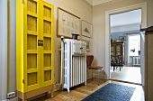 Lobby with display cabinet in an intense shade of yellow next to a radiator and open door with a view into a living room