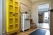 Vorraum mit kräftig gelbem Vitrinenschrank neben Heizkörper und offene Tür mit Blick in Wohnraum