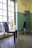 Black plastic chair in designer style in front of a balcony door and painted corner of a room