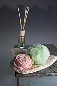 Rose soap, room scent and a massage glove on a stool