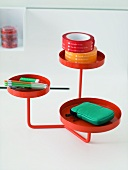 A red metal stand with round trays as a shelf for desk items
