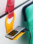 A mobile phone on a plastic yellow holder
