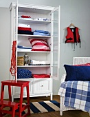 White display cabinet with open doors and the pillows and blankets inside, in front red metal step stool next to a wicker chair