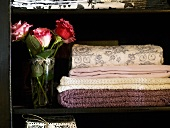 Quilted and embroidered wool blankets next to a bouquet of roses in a black cabinet